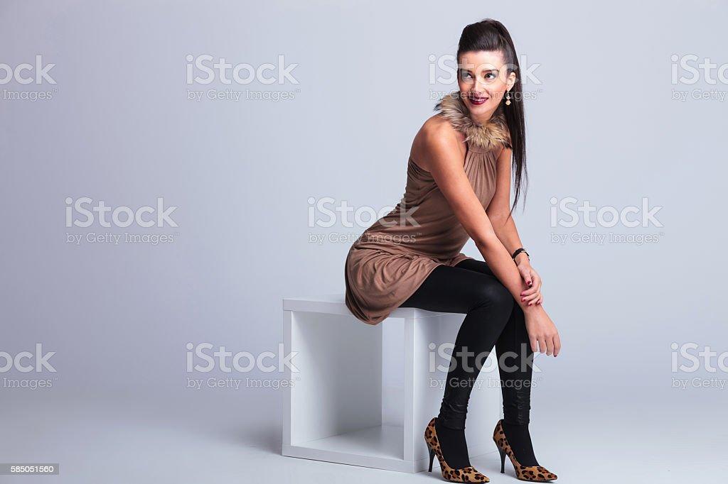 elegant fashion woman sitting on a chair while smiling stock photo