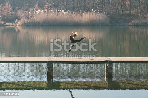 Elegant, attractive ballerina dancing outdoor on bridge across lake. Photo is taken with dslr camera ant telephoto lens on sunny autumn day in Europe.
