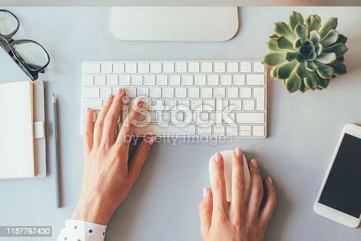 Top view of the workplace, elegant female hands on the keyboard of a personal computer in the office or at home, suitable for both freelancing and office content. Business lady prints an article or blog post online.