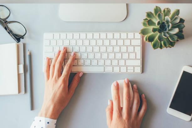 eleganti mani femminili sulla tastiera di un personal computer in ufficio o a casa - flat lay foto e immagini stock