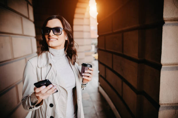 Elegant female holding smartphone and cafe cup. stock photo