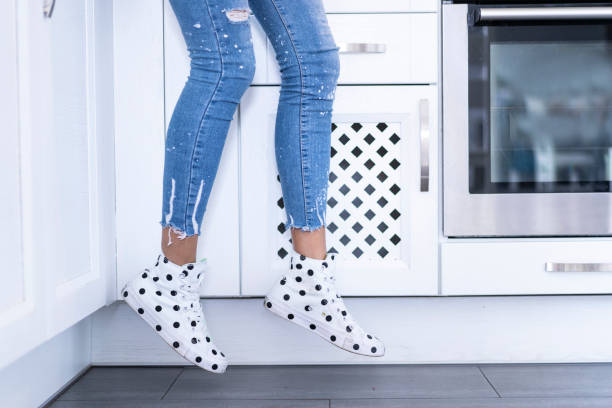 Elegant female legs in jeans and sneakers with dots stock photo