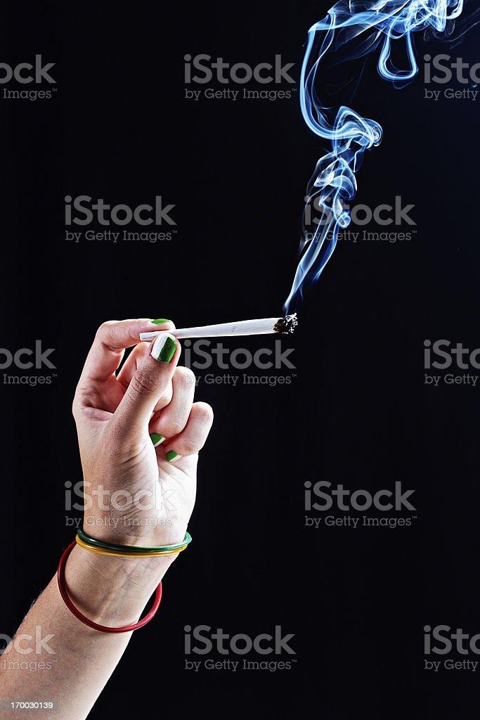 Elegant feminine hand passes hand-rolled spliff of marijuana stock photo