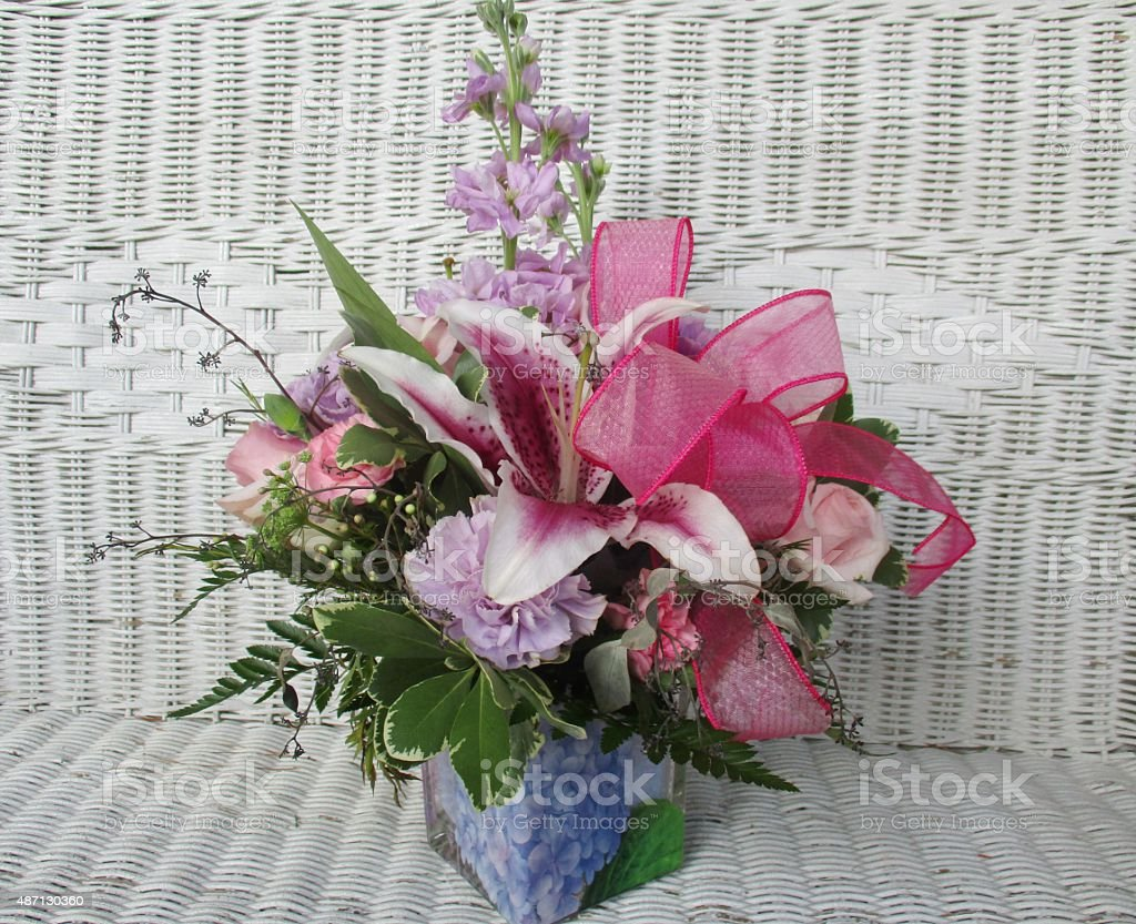 Elegant Flower Arrangement on a White Wicker Seat stock photo