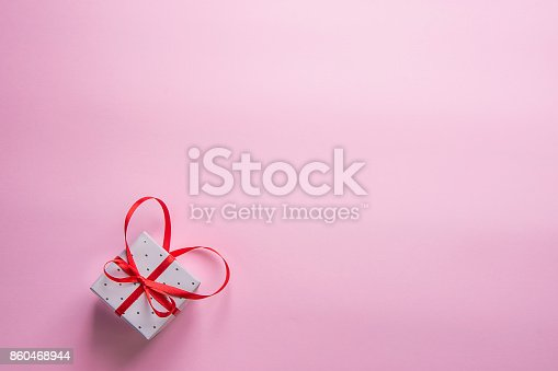 istock Elegant Gift Box Tied with Red Ribbon with Bow in Heart Shape on Pink Background. Valentine Wedding Mother's Day Birthday Women. Copy Space. Greeting Card Poster Template. 860468944