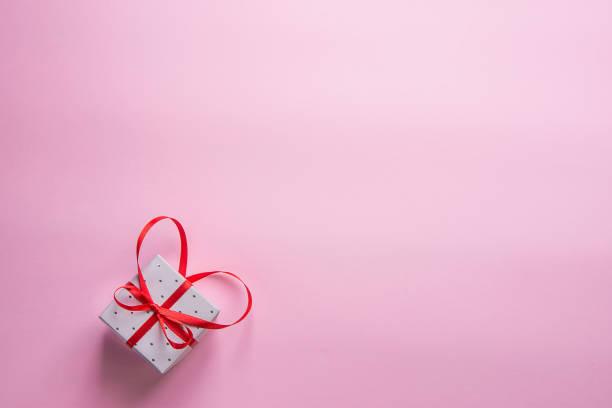 elegante geschenkbox mit schleife in herzform auf rosa hintergrund mit roten band gebunden. valentinstag hochzeit mutter tag geburtstag frauen. kopieren sie raum. grußkarte-plakat-vorlage. - originelle geburtstagsgeschenke stock-fotos und bilder