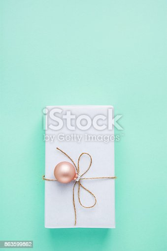 Elegant Gift Box Wrapped in White Paper Tied with Twine Pink Bauble Hanging. Christmas New Years Presents Shopping Sale. Turquoise Background Copy Space