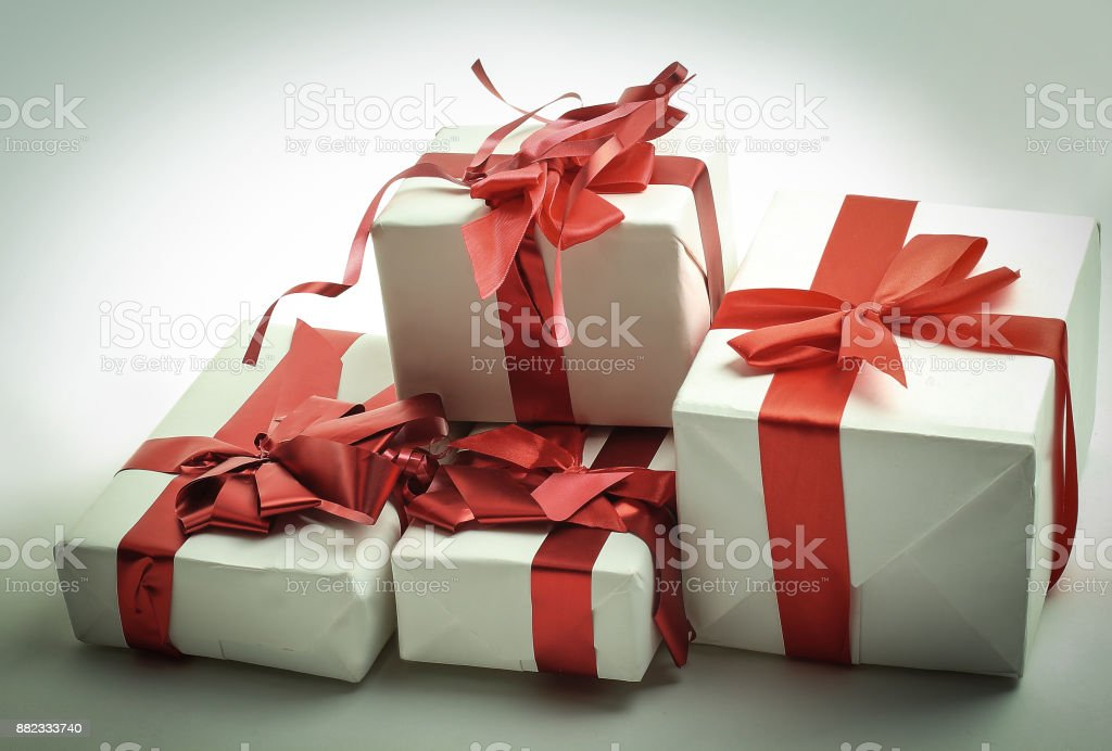 Elegant gift boxes with red satin ribbon wrapped in paper stock photo