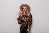 Elegant glamorous young woman with beautiful makeup with curly hair in a luxurious hat in a leopard sweater in fashionable black leather pants posing in a room near a white wall. Sexy attractive girl.