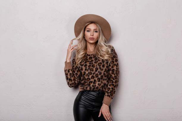 elegante glamouröse junge frau mit schönem make-up mit lockigen haaren in einem luxuriösen hut in einem leopardenpullover in modischen schwarzen lederhosen posiert in einem zimmer in der nähe einer weißen wand. sexy attraktive mädchen. - vogue muster stock-fotos und bilder
