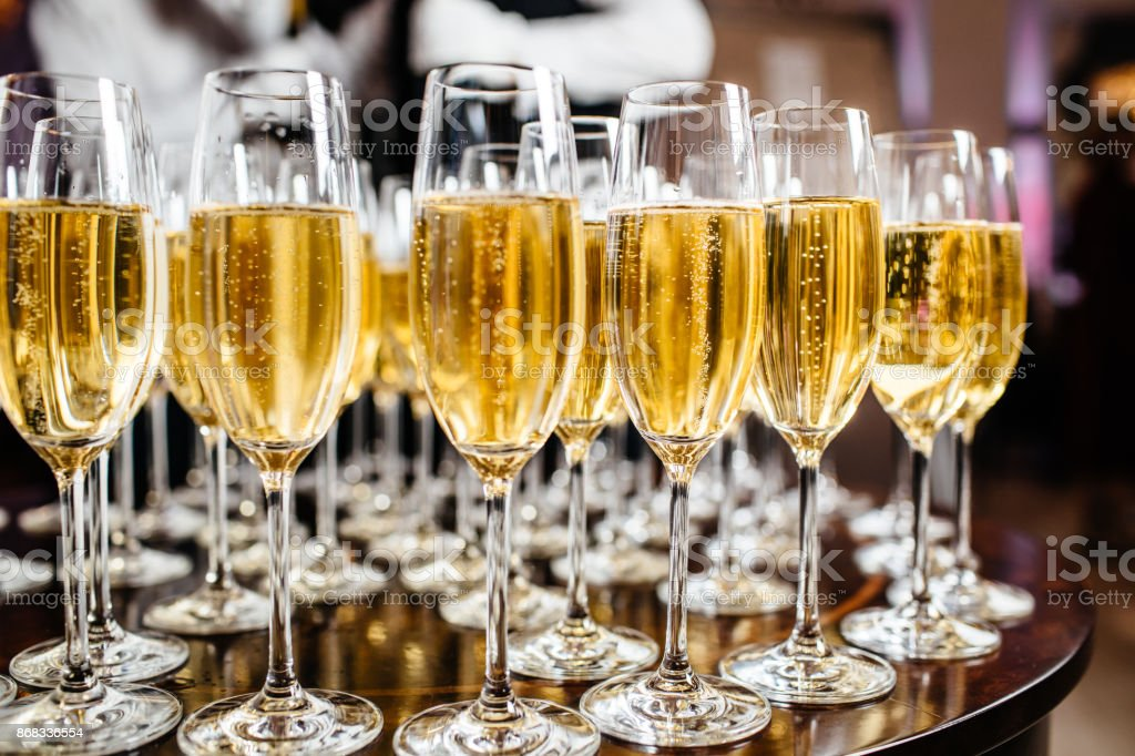 Elegant glasses with champagne standing in a row on serving table during party or celebration stock photo