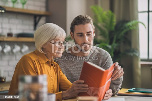 New book. Elegant good-looking grey-haired woman and her son reading a book