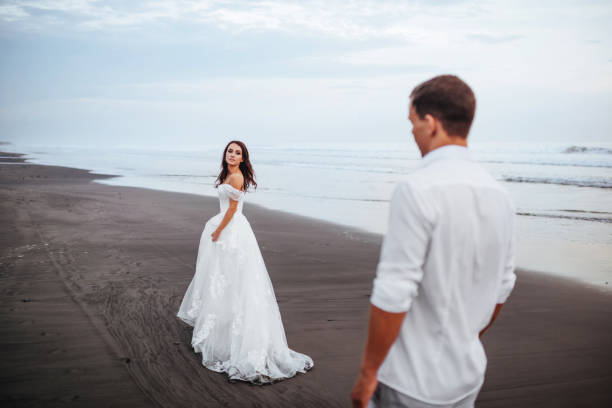 Elegant gorgeous bride and groom walking on ocean beach during sunset time. stock photo