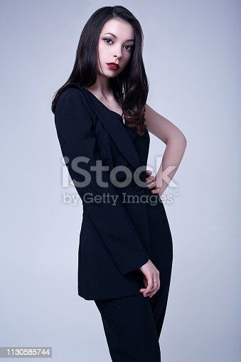 512061362istockphoto Elegant gothic brunette woman with red lips in black suit 1130585744