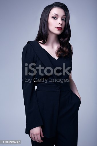 512061362istockphoto Elegant gothic brunette woman with red lips in black suit 1130585747