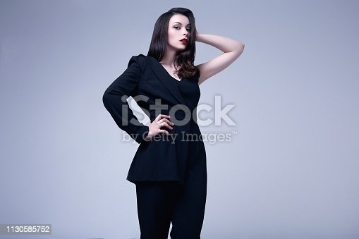 512061362istockphoto Elegant gothic brunette woman with red lips in black suit 1130585752