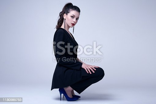 512061362istockphoto Elegant gothic brunette woman with red lips in black suit 1130585753