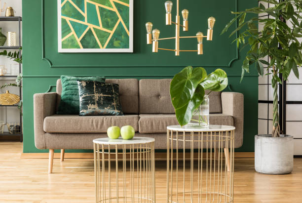 Elegantes grünes und goldenes Wohnzimmer mit komfortablem braunem Sofa, Couchtischen und goldenem Kronleuchter – Foto
