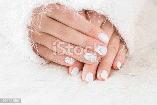 946930880istockphoto Elegant groomed woman's hands with white nails on the fluffy mat. Cares about clean, beautiful, soft hands skin and nails in winter time. Manicure beauty salon. Healthcare concept. 904421052