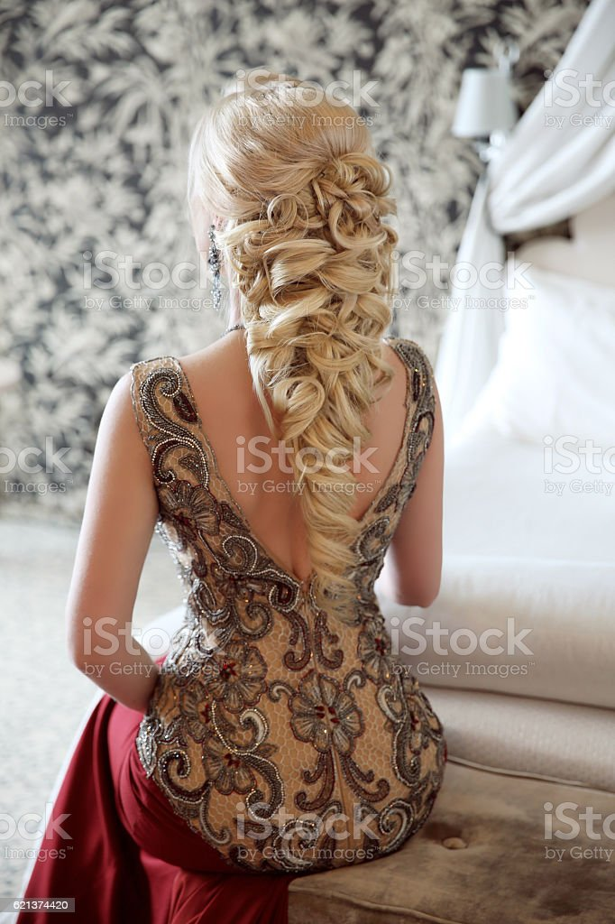 Elegant hairstyle. Beautiful blond woman in fashion red dress stock photo