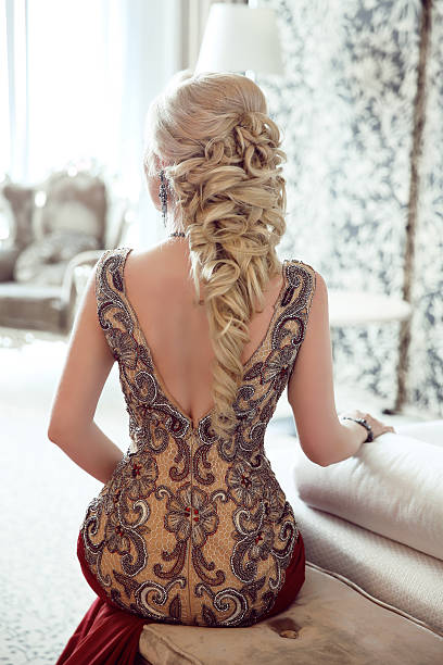 elegant hairstyle. beautiful blond woman in fashion red dress - prom fashion stock photos and pictures
