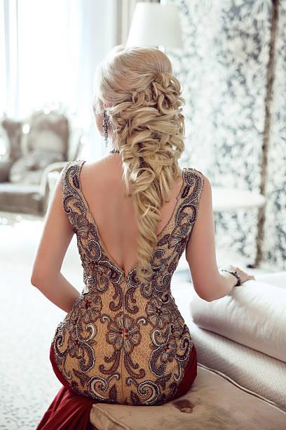 elegant hairstyle. beautiful blond woman in fashion red dress - chica rubia espaldas fotografías e imágenes de stock
