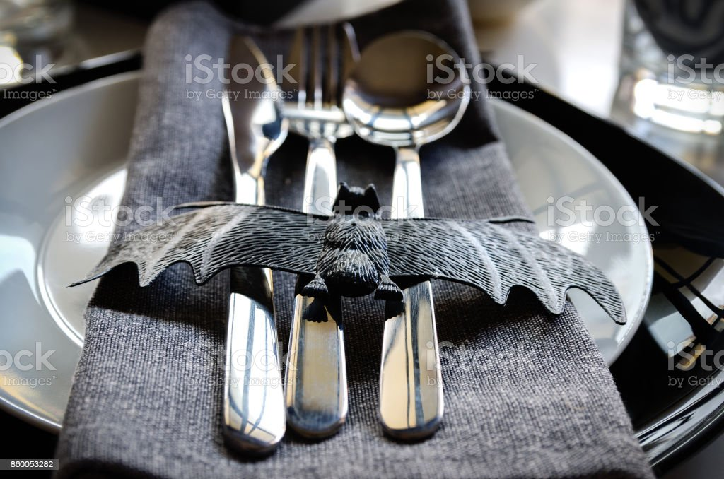 Elegant Halloween table settings in black white colors, silver cutlery and napkin ring with  bat. Halloween party concept. stock photo