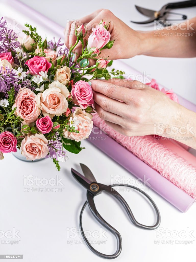 Elegant hands of a florist make a bouquet on a white background....