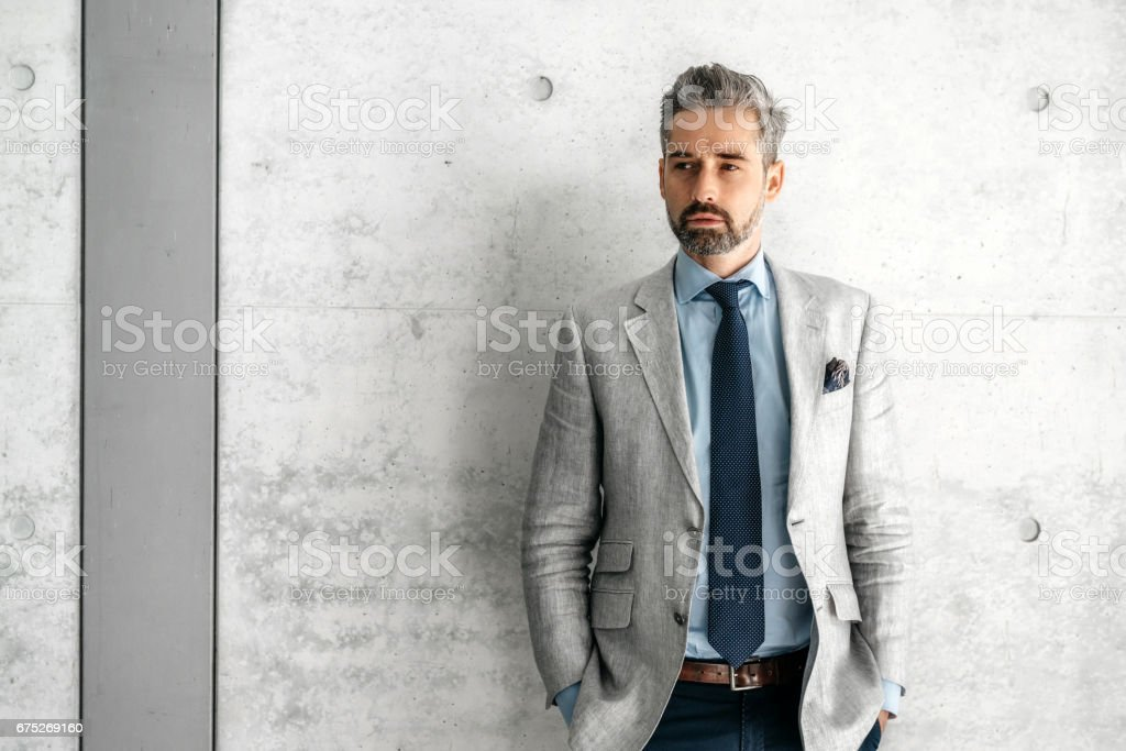 elegant handsome bearded businessman standing in front of concrete wall stock photo