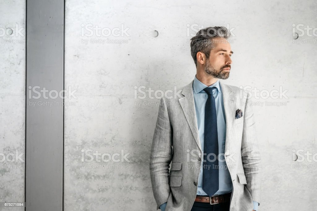 elegant handsome bearded businessman standing with dog  in business district stock photo