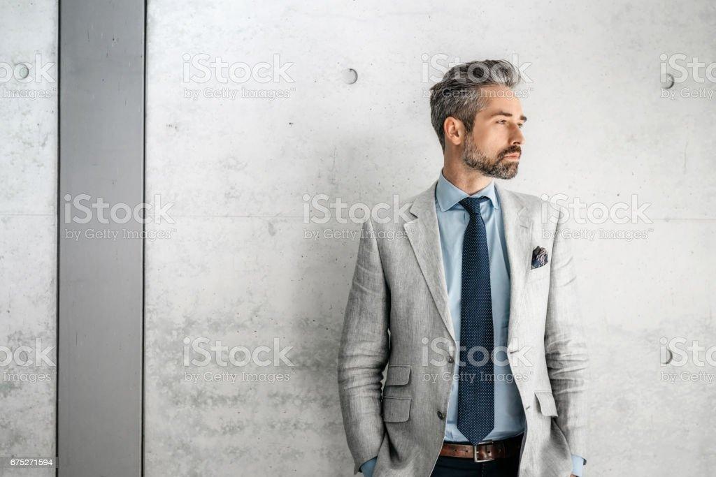 ビジネス地区の犬と一緒に立っているエレガントなハンサムなひげを生やした実業家 ストックフォト
