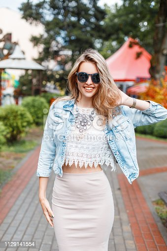 578791454istockphoto Elegant happy young hipster woman with beautiful smile in stylish clothes in sunglasses on a walk in an amusement park on a summer sunny day. Stylish positive girl on vacation. Great weekend. 1129141554