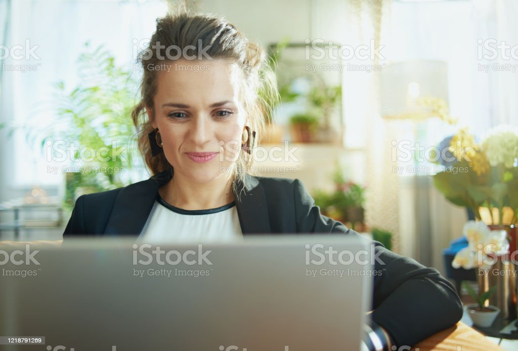 elegant housewife surfing web on laptop while sitting on couch elegant middle age housewife in white blouse and black jacket in the modern house in sunny day surfing web on a laptop while sitting on couch. Administrator Stock Photo