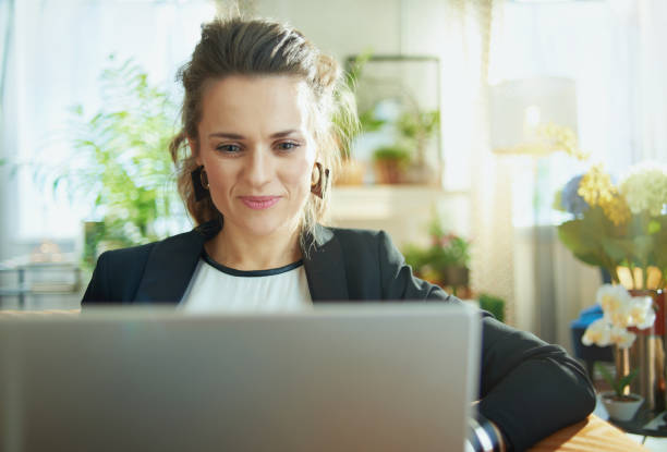 elegant housewife surfing web on laptop while sitting on couch stock photo