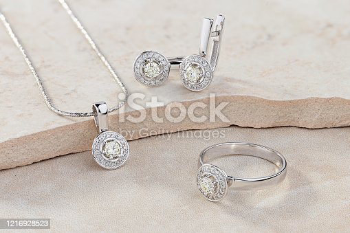 Elegant jewelry set of white gold ring, necklace and earrings with diamonds. Silver jewellery set with gemstones. Product still life concept