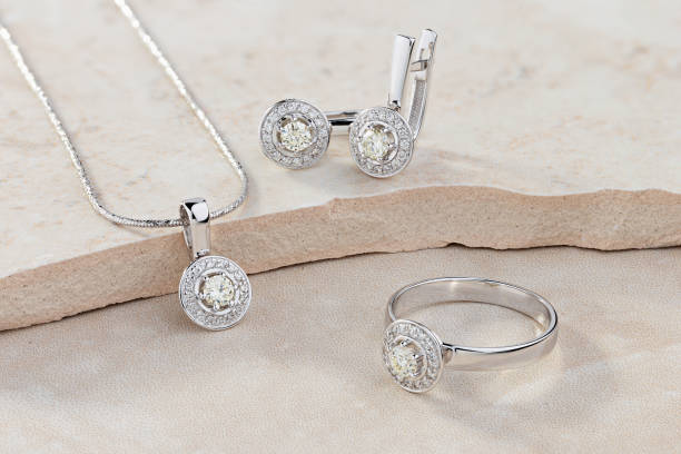 Elegant jewelry set of white gold ring, necklace and earrings with diamonds Elegant jewelry set of white gold ring, necklace and earrings with diamonds. Silver jewellery set with gemstones. Product still life concept jewelry stock pictures, royalty-free photos & images