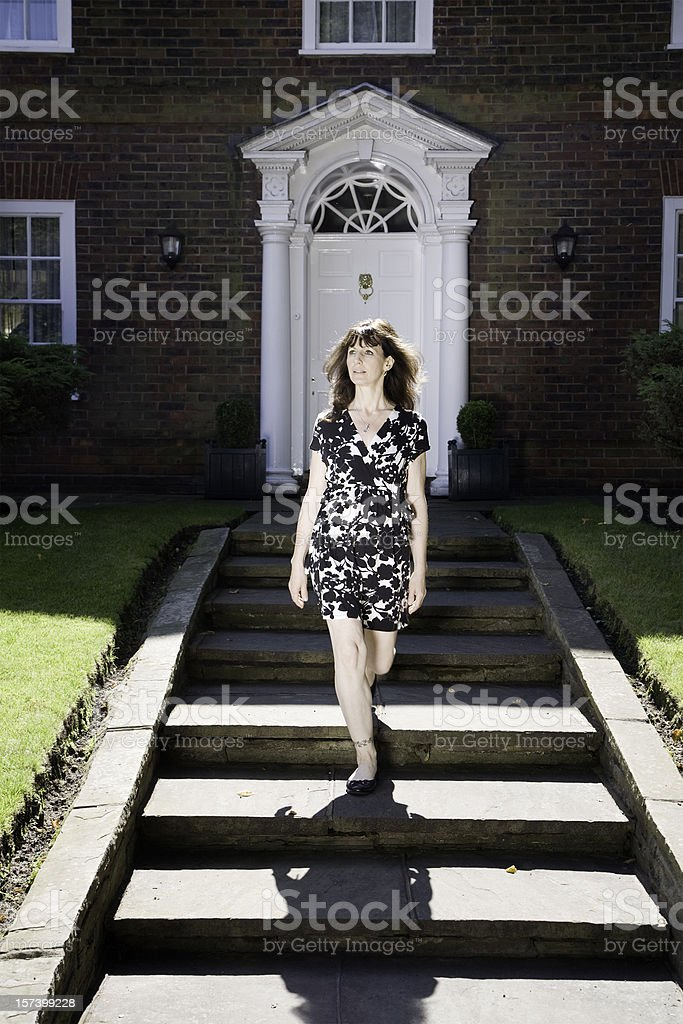 Elegant lady in front of a fancy house royalty-free stock photo