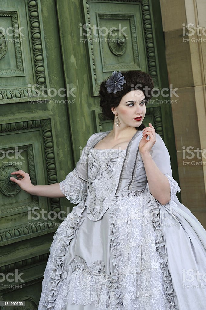 Elegant Lady in Rococo Grey Dress before Green Old Door royalty-free stock photo