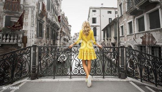 Elegant lady wearing yellow dress standing on the bridge