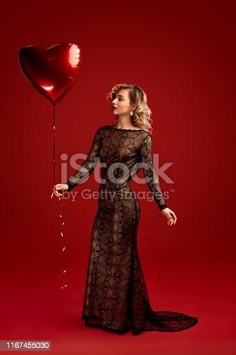 Full body slim female in black evening dress holding heart shaped balloon against vivid red background