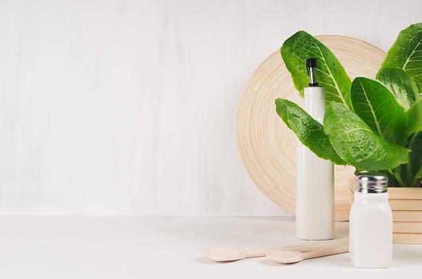 elegante leichte küche interieur mit hölzernen geschirr, keramik und grüne blätter grüns auf weiße holz-regal. - küche deko grün stock-fotos und bilder