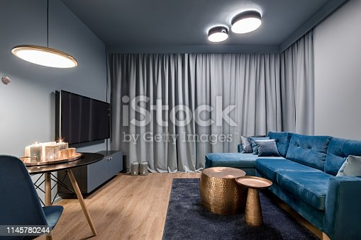 Elegant living room with big, blue sofa, two copper coffee tables and tv screen