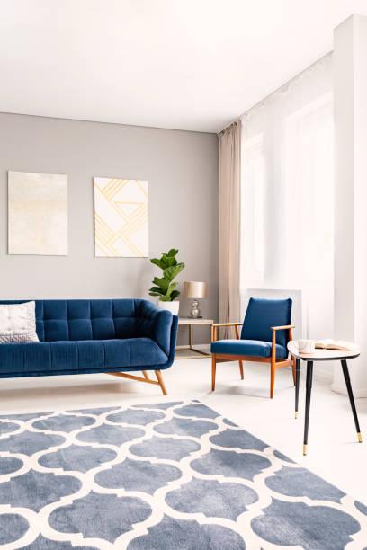 interior elegante sala de estar com um sofá azul escuro e uma poltrona correspondente. grandes janelas com cortinas e um tapete decorativo. foto real. - locais geográficos - fotografias e filmes do acervo