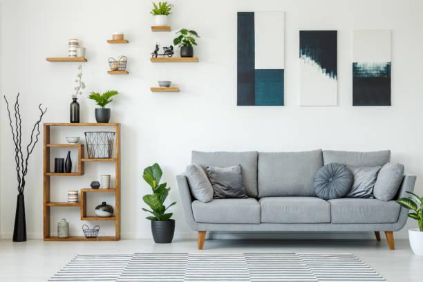 典雅的客廳內部與灰色沙發, 木架子, 植物和繪畫在牆壁上 - 畫 藝術品 個照片及圖片檔