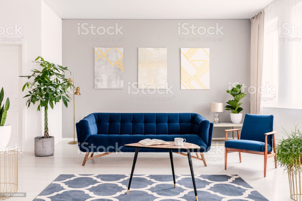 Picture of: Elegant Living Room Interior With A Set Of Dark Blue Sofa And Armchair Gold And Silver Contemporary Paintings On The Background Wall Real Photo Stock Photo Download Image Now Istock