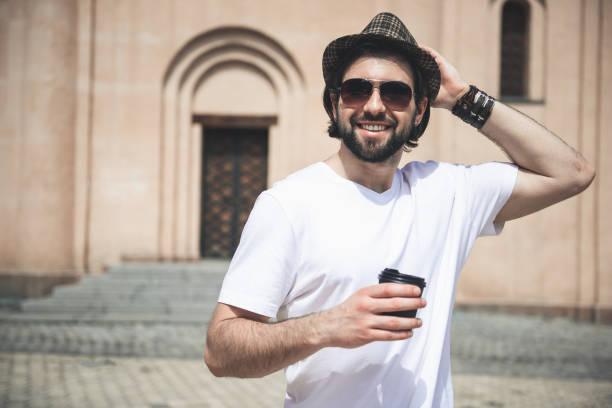 Eleganter männlicher Mensch, der mit Getränk in der Sonne steht – Foto