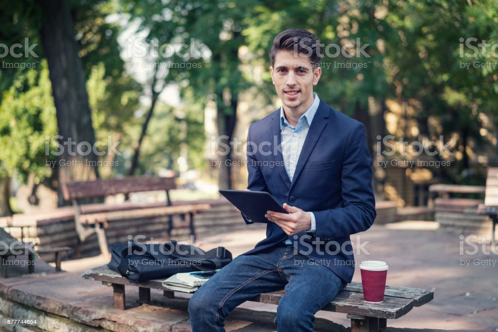 Elegant man browsing on his tablet stock photo