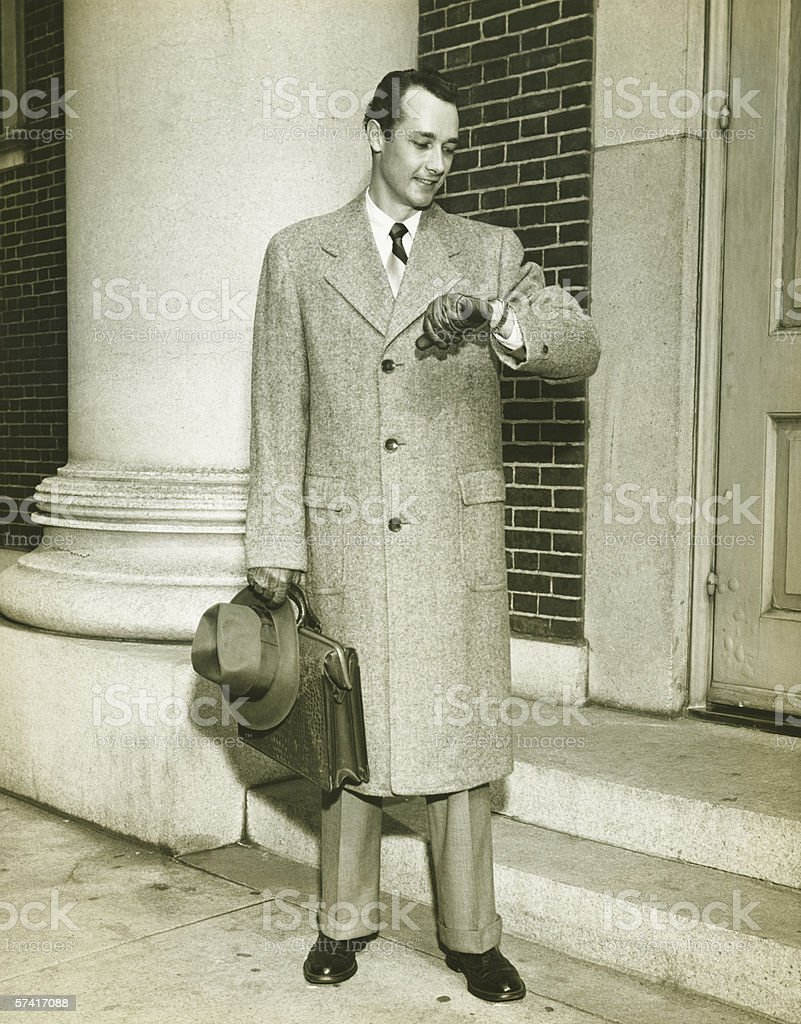 Elegant man checking watch at entrance to building, (B&W), stock photo