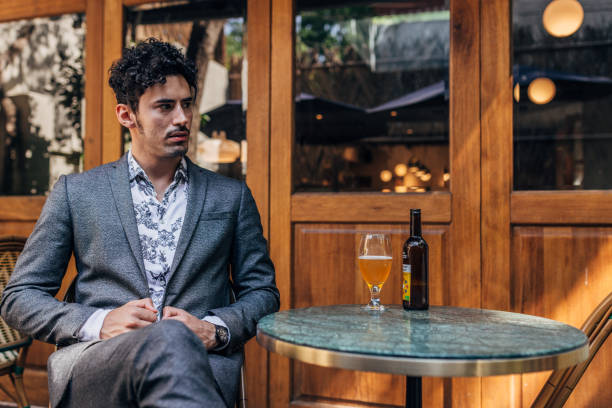 Elegant man drinking beer stock photo