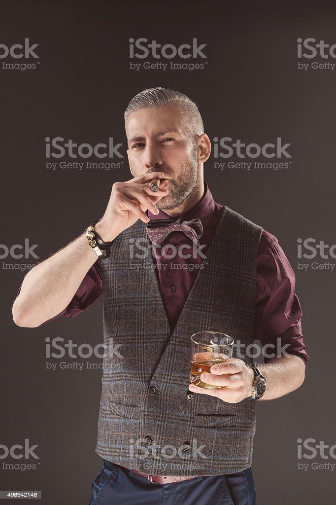 Elegant man drinking scotch whisky and smoking cigar Elegant man wearing a tweed vest and bow tie holding glass of whiskey, smoking cigar. Dark tone, black background. 2015 Stock Photo